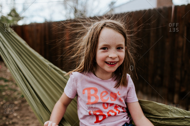 Young girl with static hair sitting on hammock