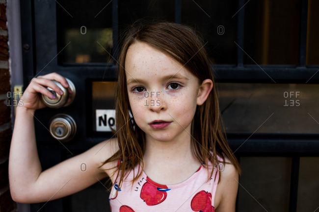 content young girl holding on to front door