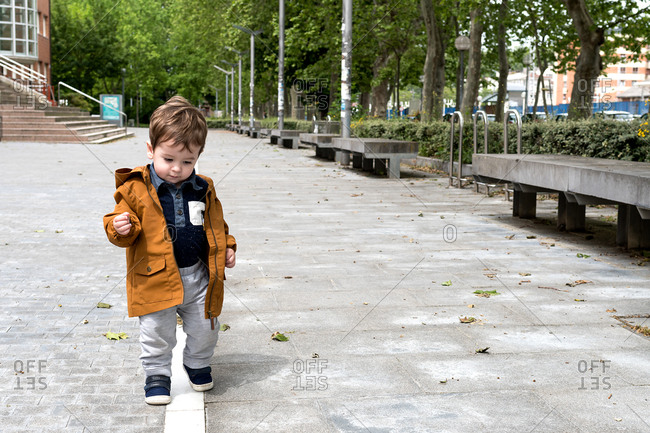 One and a half year old boy taking his first steps on the street following a white line.