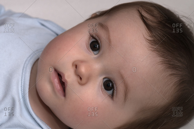 Baby about a year old, lying there staring
