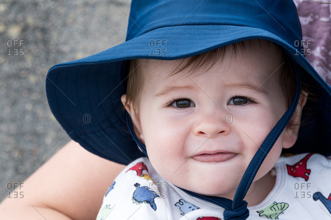 One-year-old boy, very handsome sitting on his mother's lap. He's wearing a hat