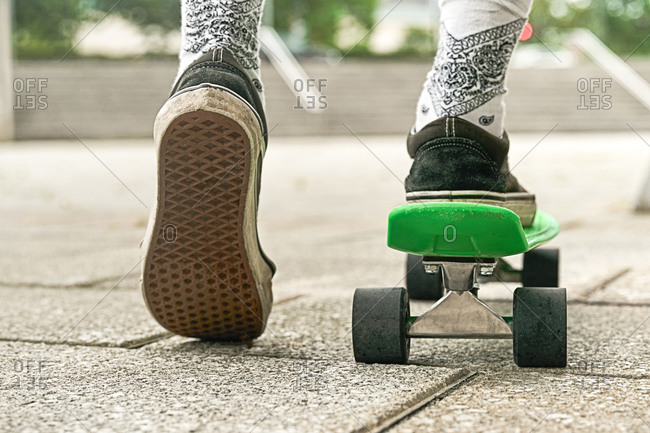 Close-up of guy legs in shorts on an outdoor penny skateboard