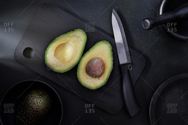 Avocado on a cutting table ready to cut. black background