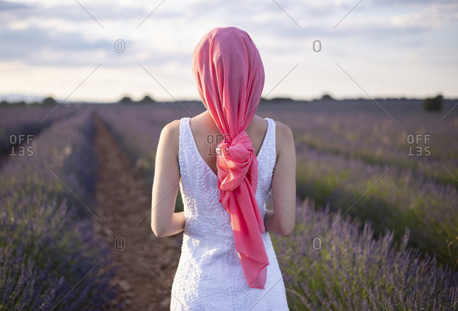 Woman with pink cancer scarf in a lavender field