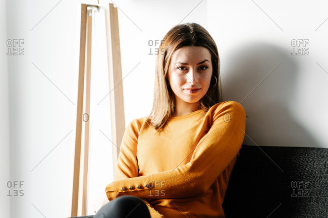 Young woman in an orange jersey waits in a clinic.