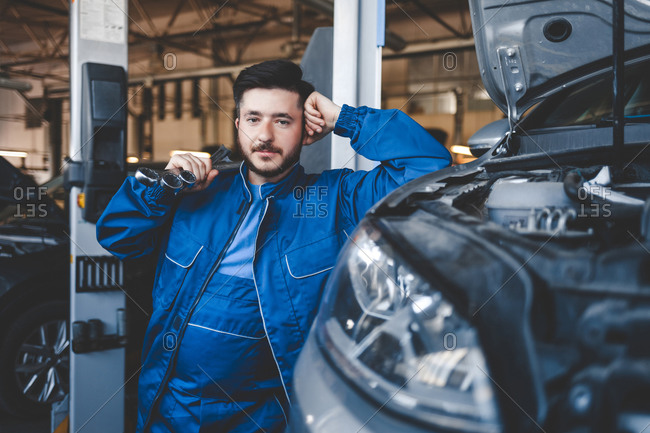 Portrait of a male car mechanic with wrenches