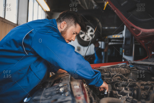 Male auto mechanic in blue uniform is repairing a car
