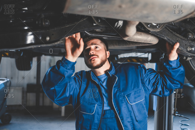 Auto mechanic inspects car suspension.