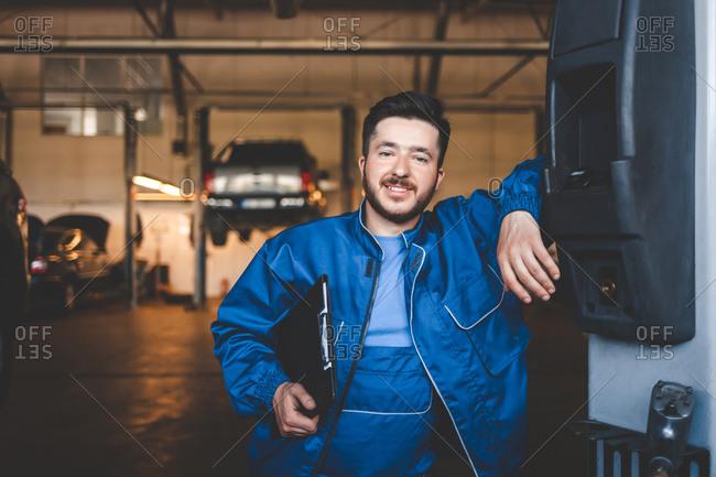 Portrait of a positive car mechanic in a garage