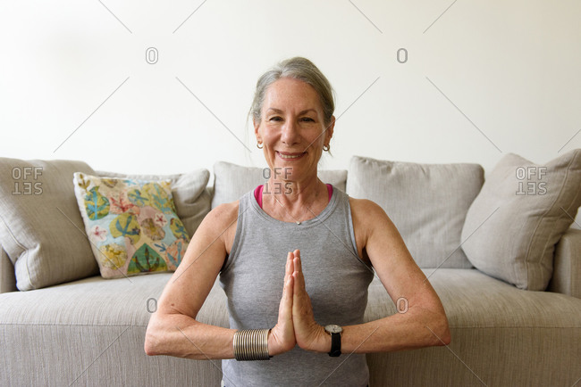 Smiling older woman holding hands to heart in yoga pose by couch