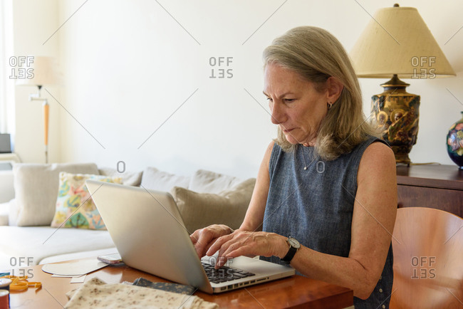 Senior woman typing on laptop at home table with sewing hobby