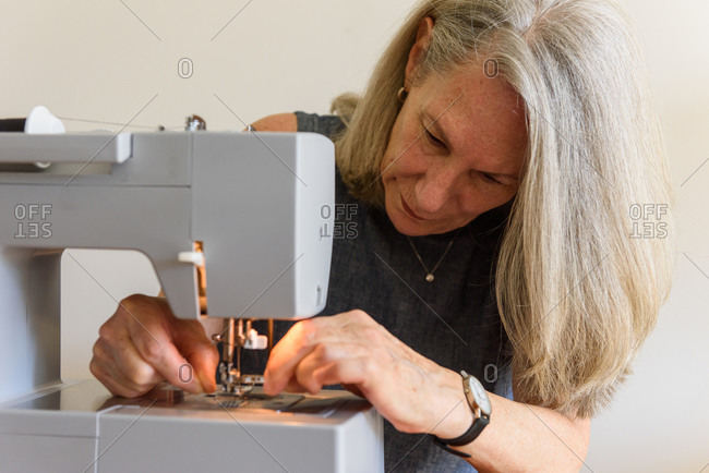Older woman starting hobby of mask making and threading sewing machine