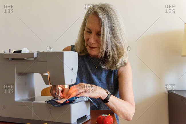 Woman sewing cloth masks on home machine