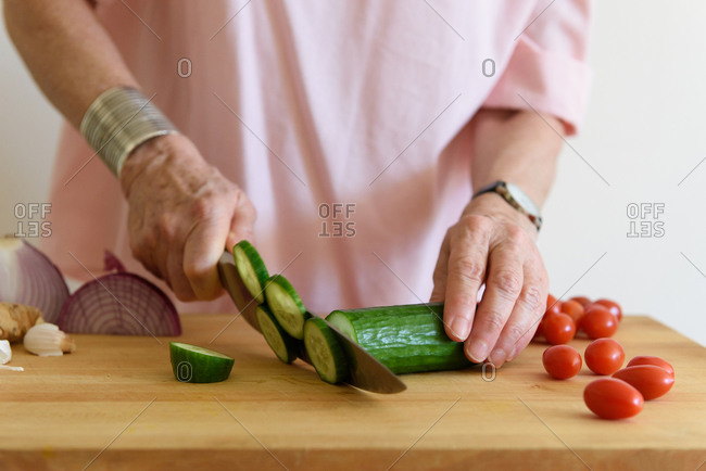 Close up of older woman's hands cutting cucumbers on chopping block