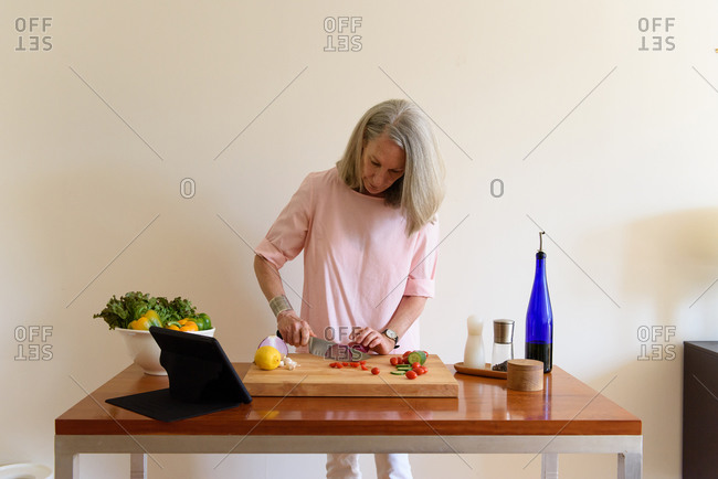 Senior woman chopping fresh vegetables and looking at tablet recipe
