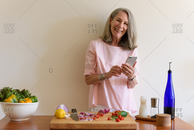 Senior woman looking to camera and holding phone at cutting board