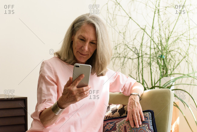 Senior woman reading messages on phone in apartment