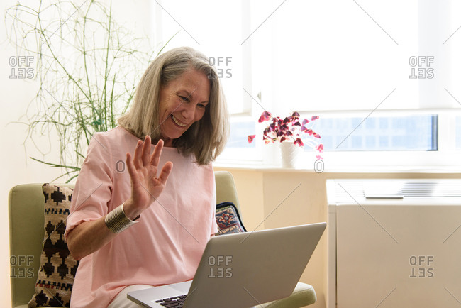 Senior woman waving to laptop on remote meeting at home