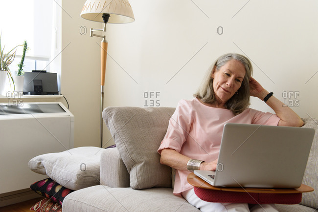 Senior woman sitting on couch with laptop at home
