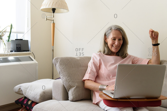 Older woman laughing while looking at laptop from apartment couch