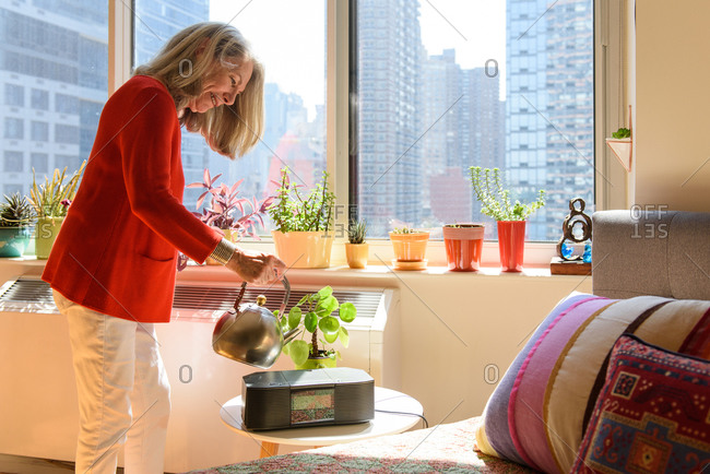Older woman watering plants in bedroom from midtown apartment