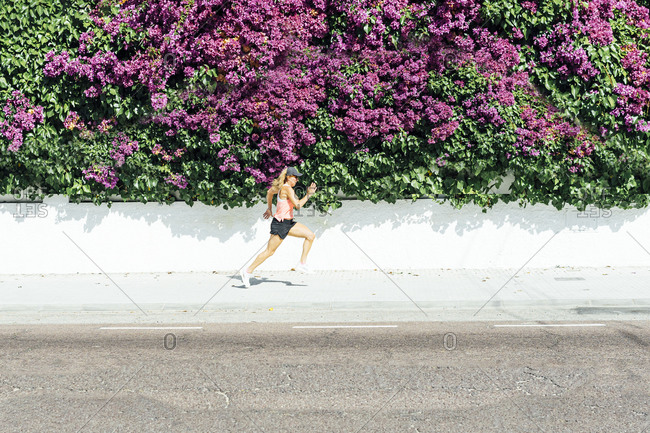 Woman jogging on street , with colorful flowers background