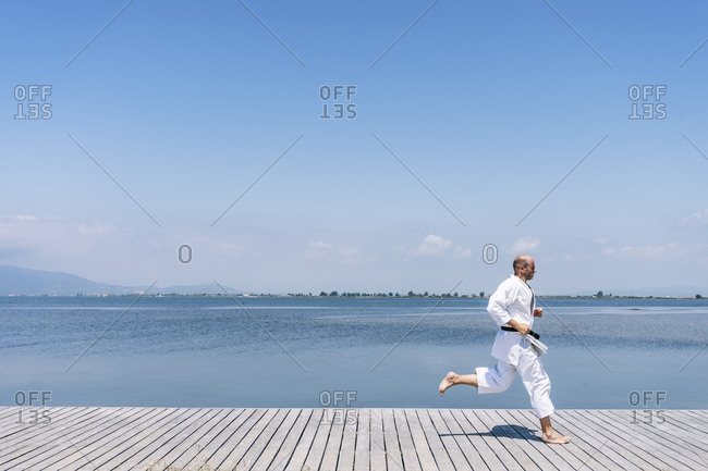 A man practices martial arts running on a wooden walkway by the sea