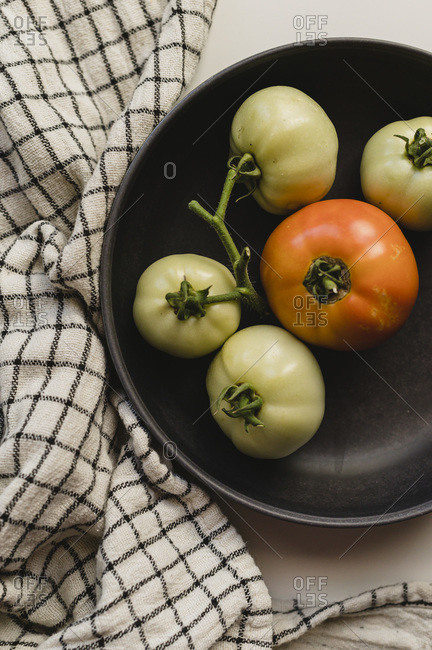 Homegrown Green and Orange Tomatoes in a Black Bowl