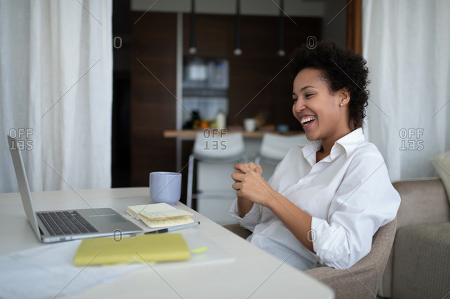 Happy mixed race businesswoman during online meeting