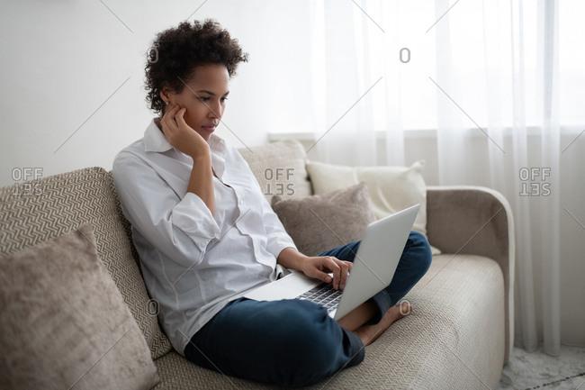 Serious African American freelancer using laptop
