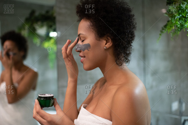 Delighted mixed race woman applying clay on face
