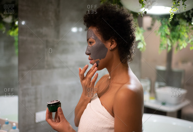 African American woman smearing clay mask