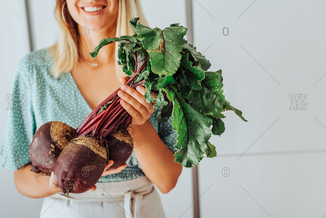 Young woman midsection holding beetroots with green leaves and smiling