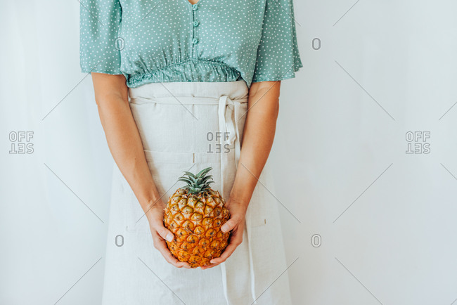Midsection of a woman holding pineapple in front of her