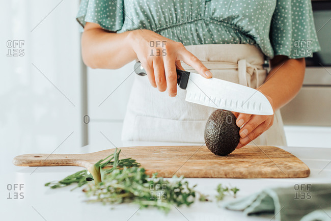 Close up of female hands holding a kitchen knife to cut avocado