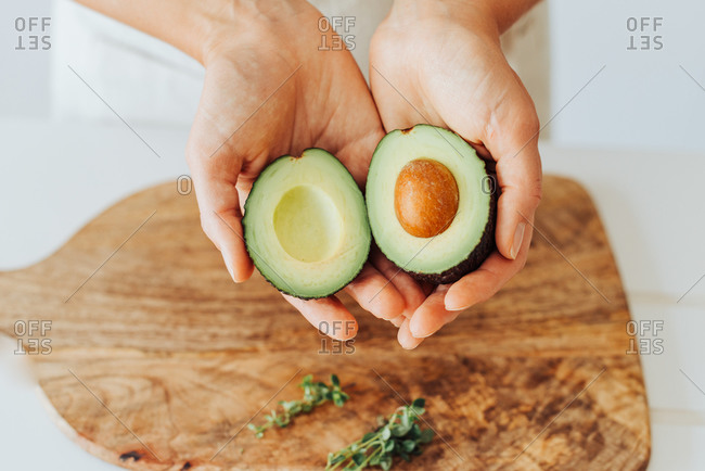 Close up of hands holding fresh avocado, source of healthy fats