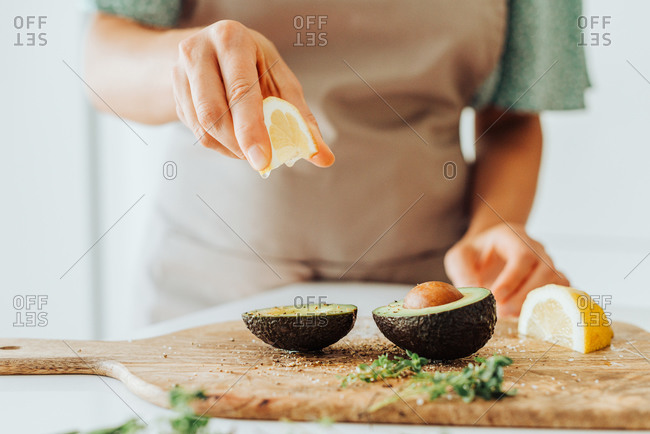 Female hands squeezing lemon while preparing a meal with avocado