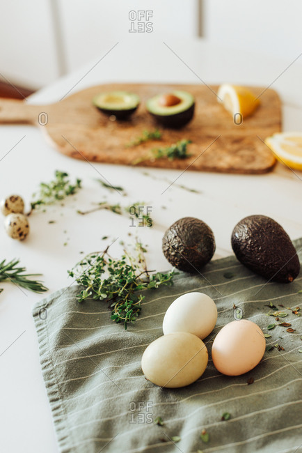 Ingredients for a meal: avocado, eggs, aromatic herbs on a table