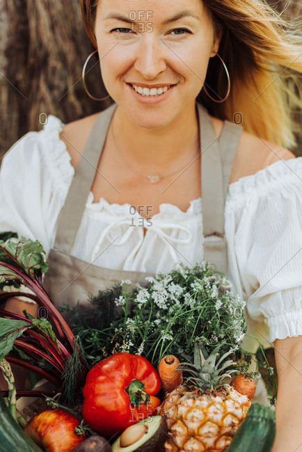 Close up of young woman holding basket of vegetables and smiling