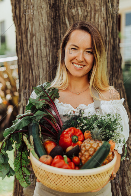 Young smiling woman with basket of vegetables standing against a tree