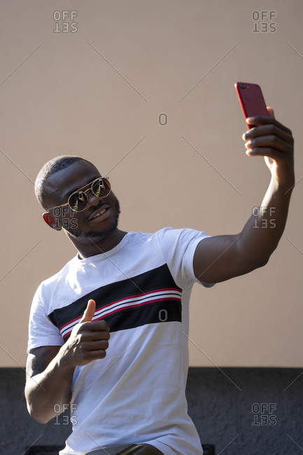 Man with sunglasses using mobile cell phone.