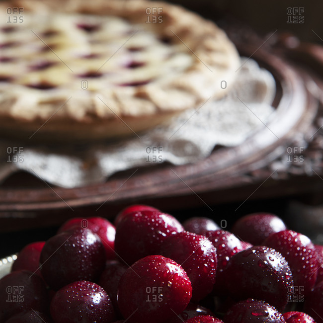 Fresh cherries ,cooked pie in the background blurred for text overlay