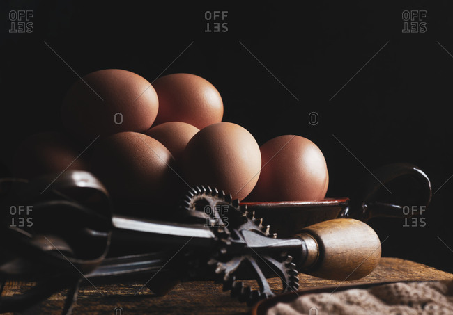 Organic chicken eggs  on wood with a iron whisk, dark background