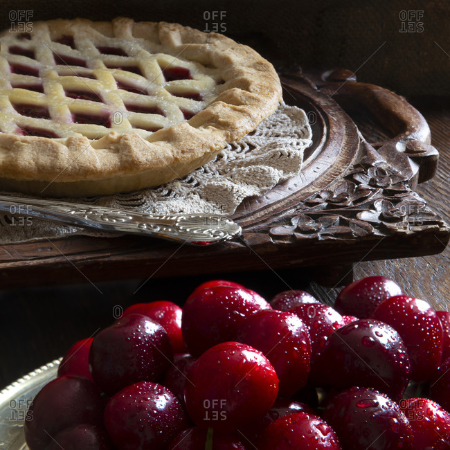 Cherry pie with  fresh washed organic cherries in the foreground