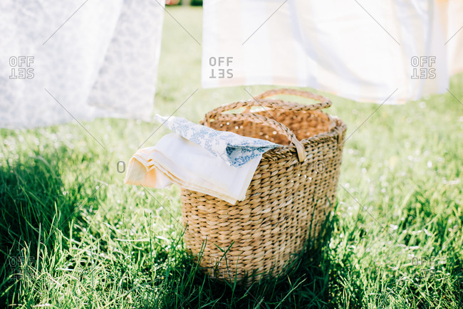 Wicker basket filled with bed linen in a yard at home in summer