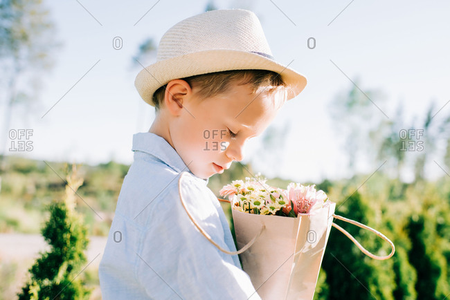 Handsome young boy looking at a beautiful bouquet of flowers