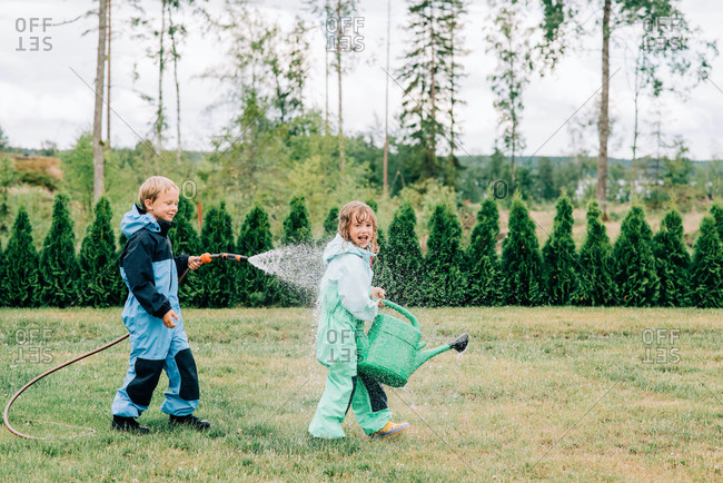 Brother and sister playing in the rain with a hose and watering can