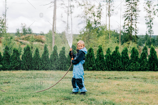 Boy standing with a hose spraying water at home in the yard