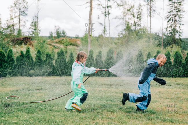 Sister spraying her brother with a hose whilst playing in the rain