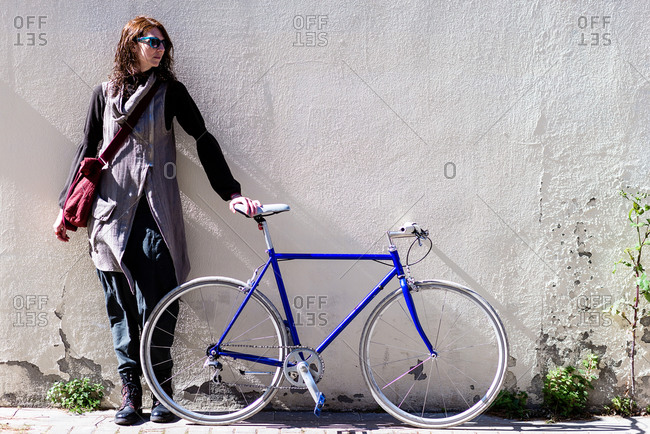 Young woman leaning on a city wall with vintage bike in sunny day